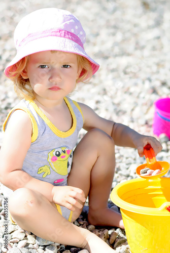 little girl playing on the beach in the summer
