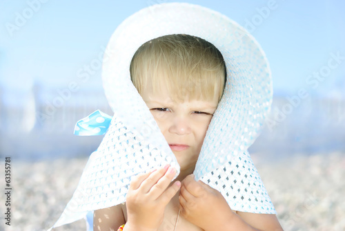a little girl in large hat on the shore of the sea in the summer