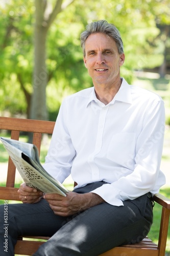 Businessman holding newspaper in park