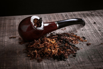 pipe and tobacco on wooden surface