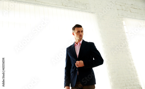 Confident fashion businessman standing in office