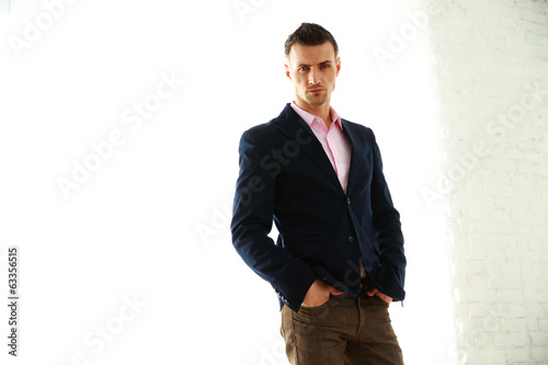 Confident fashion man standing over white background