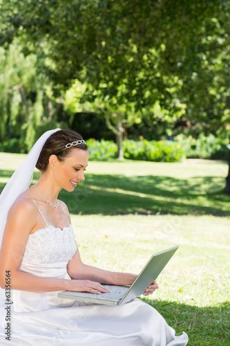 Bride using laptop on grass at garden