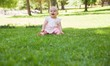 Cheerful cute baby sitting on grass at park