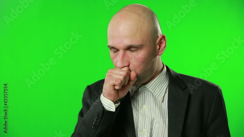 Sick businessman coughing against a green screen