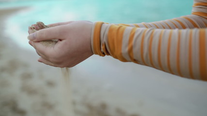 Sand pouring out of female hands