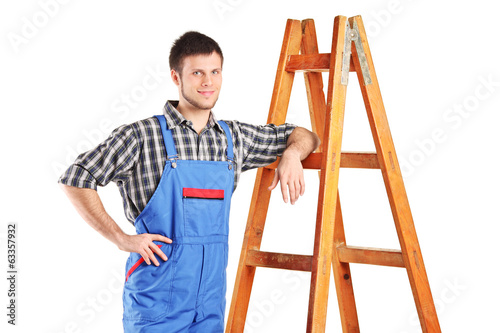 Male worker in jumpsuit standing next to a ladder