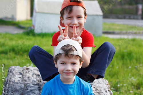 Happy little boys in cap at outdoor, childhood