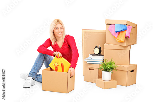 Young girl sitting with moving boxes next to her