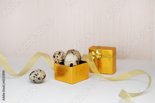 golden box with Easter eggs and ribbon