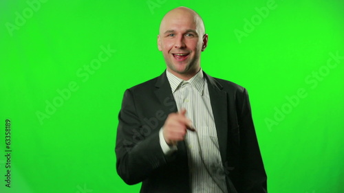 Young businessman pointing on something against a green screen.