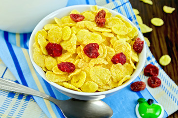 Cornflakes with dried cherries and milk on board
