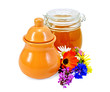 Honey in a jug and jar with flowers