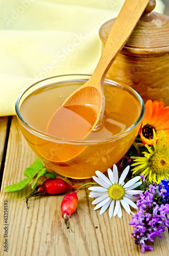 Honey with flowers and spoon on board