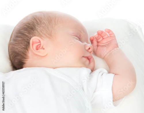New born infant child baby girl sleeping on a back in white shir