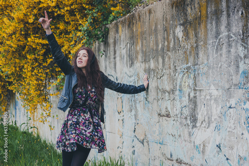 Pretty girl with long hair leaning against a concrete wall