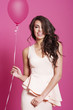 Attractive happy brunette women with pink balloon