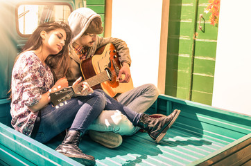 Romantic young Couple of lovers playing Guitar outdoors