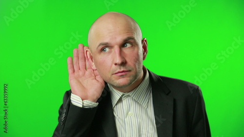 Young businessman eavesdropping against a green screen