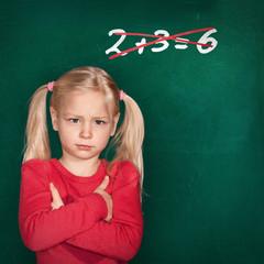 Mädchen vor Schultafel mit falscher Rechenaufgabe