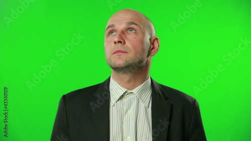 Young businessman looking around against a green screen