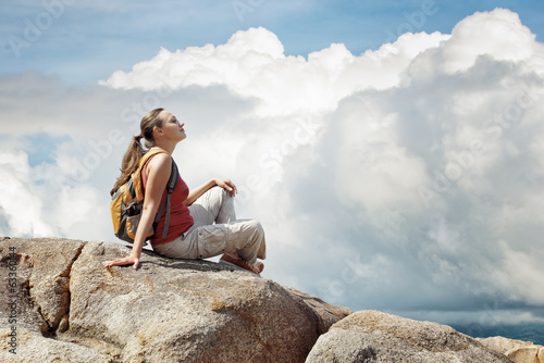 Young woman sitting on a rock with backpack.