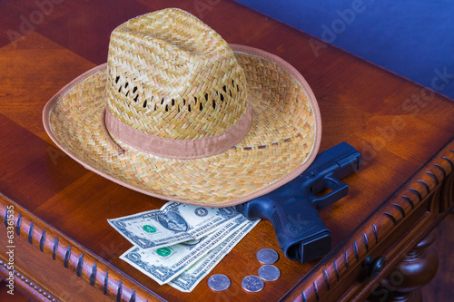 Hat, Handgun and money on wooden desk