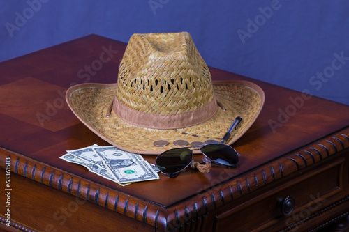Hat, sunglasses and money on wooden desk