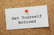 The phrase Get Yourself Noticed on a cork notice board