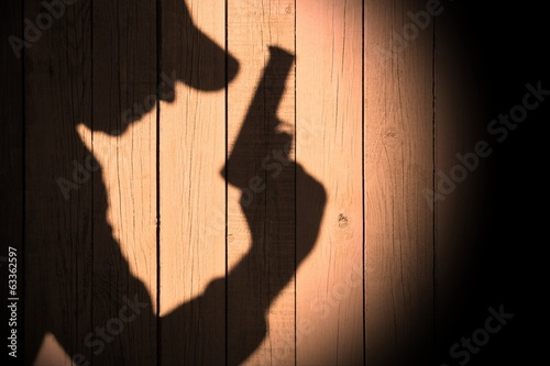 Investigator or Gangster or spy silhouette on natural wooden wal