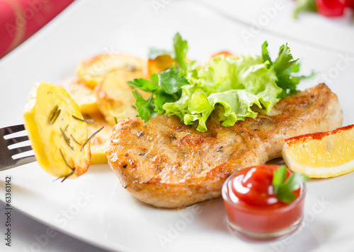 Roasted pork chop with potatoes, ketchup and lemon on dish