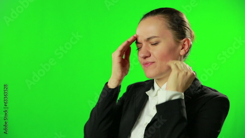 Young woman with headache against a green screen