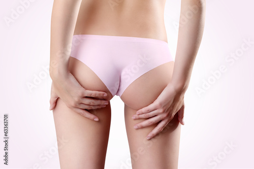 Bum and legs of woman, hands touching the buttocks over pink bac