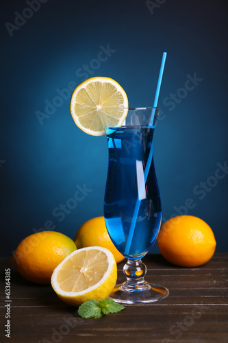 Glass of cocktail on table on dark blue background