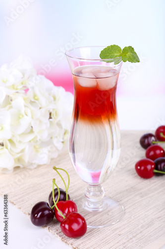 Glass of cocktail on table on light background