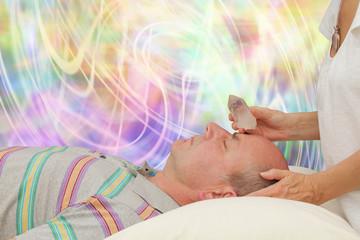 Crystal healer balancing third eye chakra