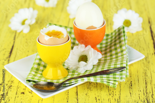 Boiled eggs on color wooden background