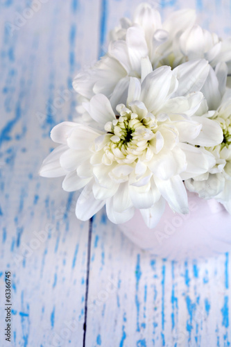 Beautiful chrysanthemum flowers in vase on wooden table