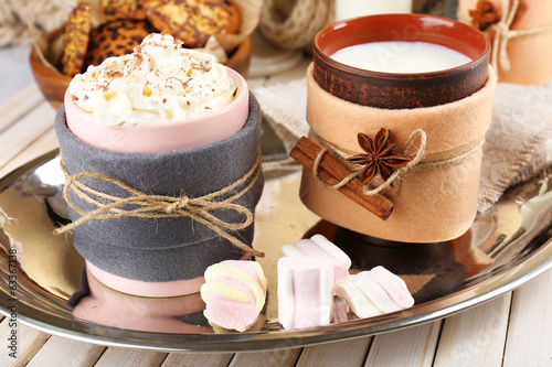 Mug of hot drink decorated in felt on wooden table