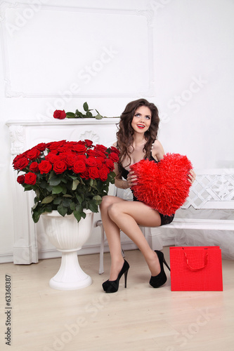 Happy smiling beautiful woman holding red heart over bouquet of