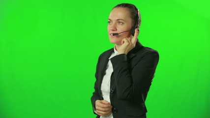 Smiling call center woman with headset against a green screen