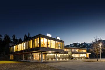 illuminated modern wooden office building at night