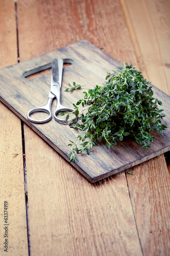 Bunch of fresh thyme and scissors, on wooden chopping board