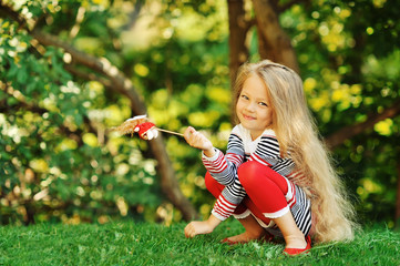 Photo of cute little girl sitting on green grass