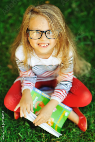 Attractive little girl with book in a park