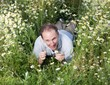 man lies in flowers of camomile