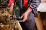 Carpenter at work with electric planer joinery poster