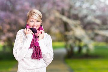 junge blonde Frau vor Kirschbaumhintergrund