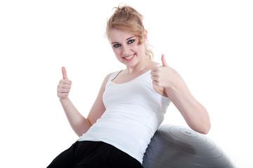 Frau beim Sport zeigt lächelnd Daumen hoch