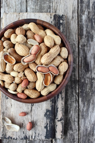 Peanuts in the wooden bowl on rustic table.